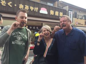 Matt is standing next to his parents. All three of them are biting into their own Fushimi Inari Sparrow on a stick. It does not look like a pleasant experience.