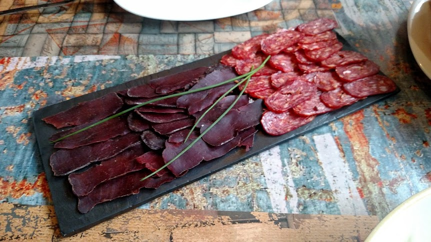 Thinly sliced meat is arranged on a platter ready to eat. The darker meat on the left is horse and the light red meat on the right is pork.