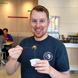 Matt is smiling with a small cup of natto in his left hand and chopsticks in his right hand. The soybean mush is gripped by the chopsticks with a trail of goo leading back into the cup. He is smiling despite the fact that he is about to eat something gross.