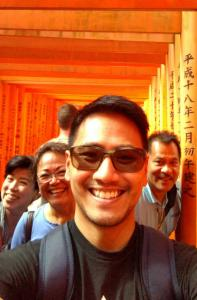 Jason's family is smiling beneath many bright red torii gates of Fushimi Inari Shrine. The gates are lined up one after the other in the background forming a tunnel.