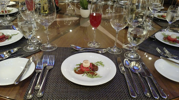 AmaWaterways Chef's Table Chef's Welcome is a simple arrangement of three layers: marinated heirloom tomatoes on the bottom, a disc of watermelon in the middle, and caramelized goat cheese on top. Bits of frisee are haphazardly distributed around the white plate.
