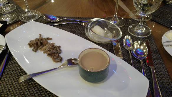 AmaWaterways Chef's Table Soup Course has a thick, opaque soup in a small bowl on top of a rectangular white plate with oyster mushrooms. Behind it sits a glass shaped like a raindrop cut in half containing pear sherbert and sparkling wine.